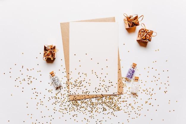 Nota em branco com envelope, presentes e estrelas de glitter dourados sobre fundo branco