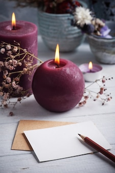 Nota em branco vazia e envelope kraft com marsala acendeu velas na mesa de madeira branca. copie o espaço para texto, para saudação, convite