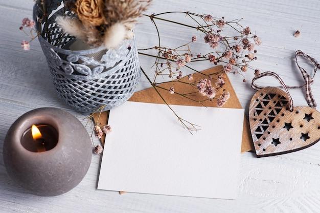 Nota em branco vazia e envelope kraft com vela acesa na mesa de madeira branca. copie o espaço para texto, para saudação, convite