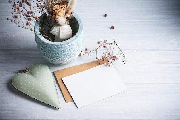 Nota em branco vazia e envelope kraft com velas acesas e coração verde na mesa de madeira branca. copie o espaço para texto, para saudação, convite