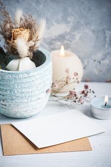 Nota em branco vazia e envelope kraft com velas acesas na mesa de madeira branca. copie o espaço para texto, para saudação, convite