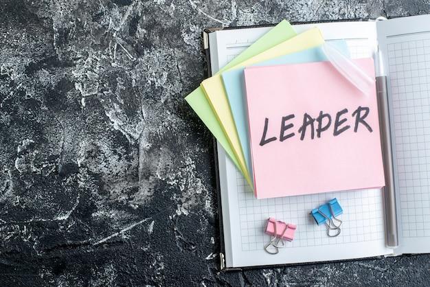 Nota escrita do líder de vista superior com adesivos e caderno em fundo cinza