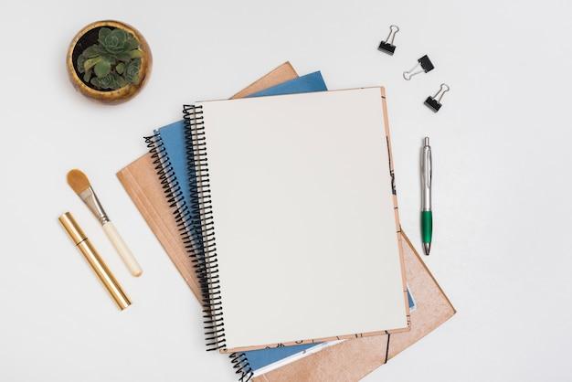 Nota espiral em branco com pincel de maquiagem; rímel; clipes de papel e caneta com planta em vaso na mesa branca