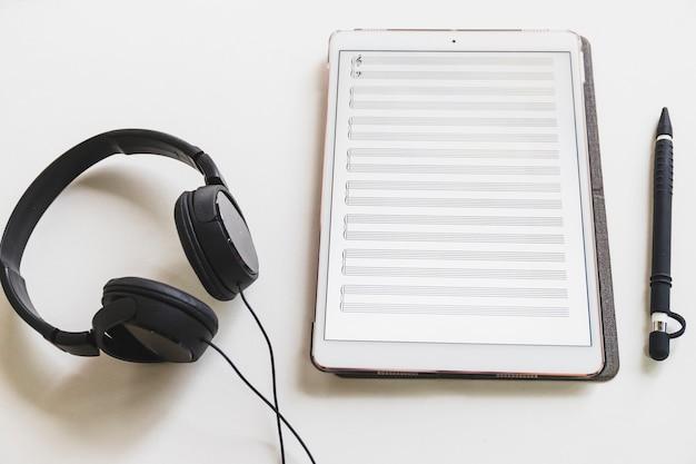 Nota musical na tabuleta gráfica digital; caneta stylus e fone de ouvido no fundo branco