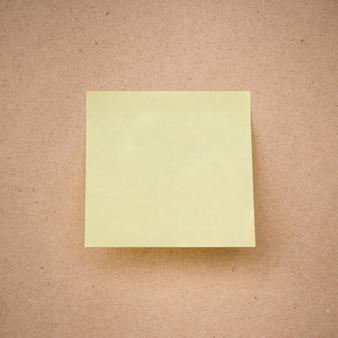 Nota pegajosa amarela na textura de papel marrom close-up