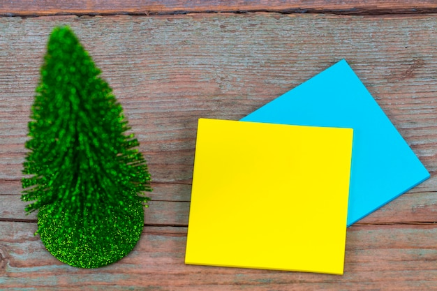 Nota pegajosa com espaço vazio para um texto e a árvore de natal com fundo de madeira.