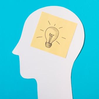 Nota pegajosa com ícone de lâmpada sobre o papel cortado a cabeça