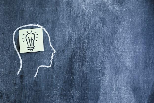 Nota pegajosa de lâmpada no contorno de rosto desenhado com giz no quadro-negro