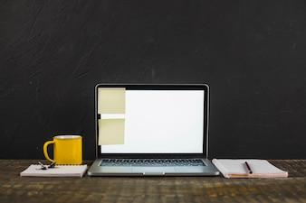 Nota pegajosa no laptop de tela em branco branco com caneca de café e artigos de papelaria sobre a mesa de madeira