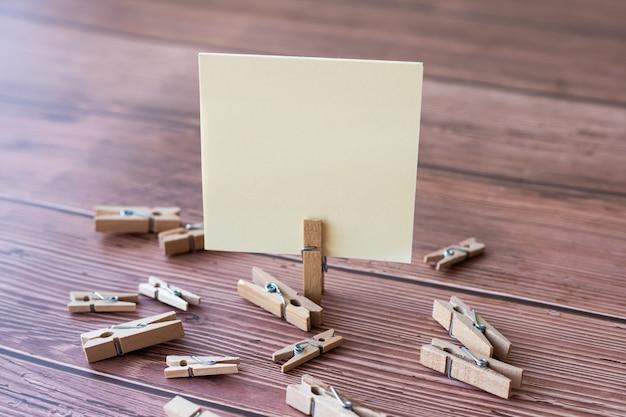 Nota quadrada em branco cercada por clipes de roupa suja mostrando um novo significado em um pedaço vazio de papel colante