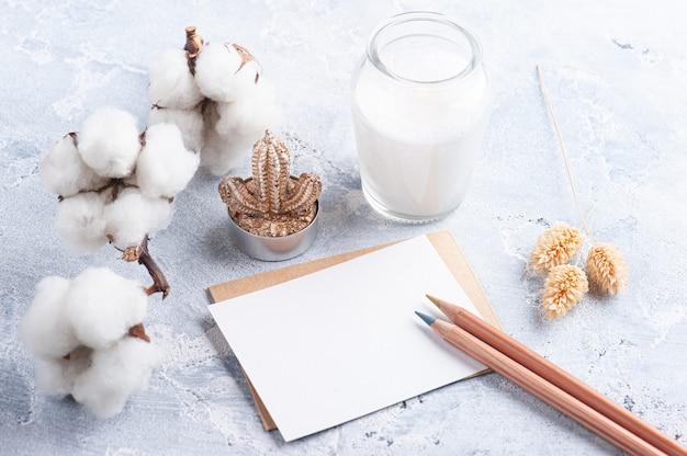 Nota vazia e envelope kraft com lápis. flor e vela de algodão em frasco de vidro em fundo branco de concreto