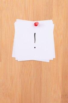 Notas adesivas brancas com ponto de exclamação fixadas no quadro de mensagens de madeira