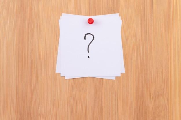 Notas adesivas brancas com ponto de interrogação afixado no quadro de mensagens de madeira