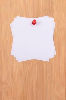 Notas adesivas brancas fixadas no quadro de mensagens de madeira