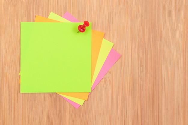 Notas adesivas coloridas fixadas no quadro de mensagens de madeira