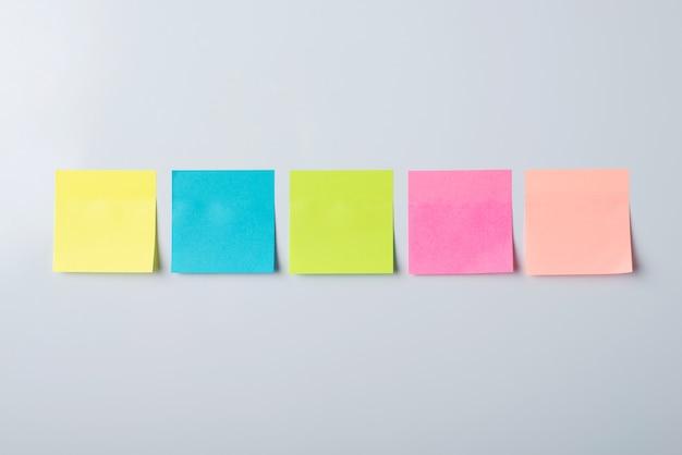 Notas adesivas de cores diferentes no quadro magnético branco
