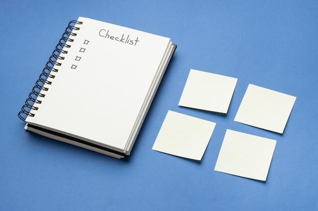 Notas adesivas de vista superior com lista de tarefas e caderno ao lado