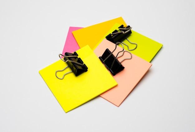 Notas adesivas em branco de cores diferentes com pastas pretas sobre fundo branco