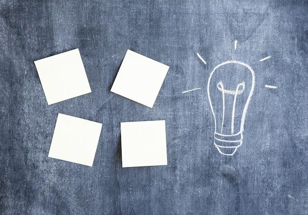 Notas adesivas em branco e lâmpada desenhada na lousa