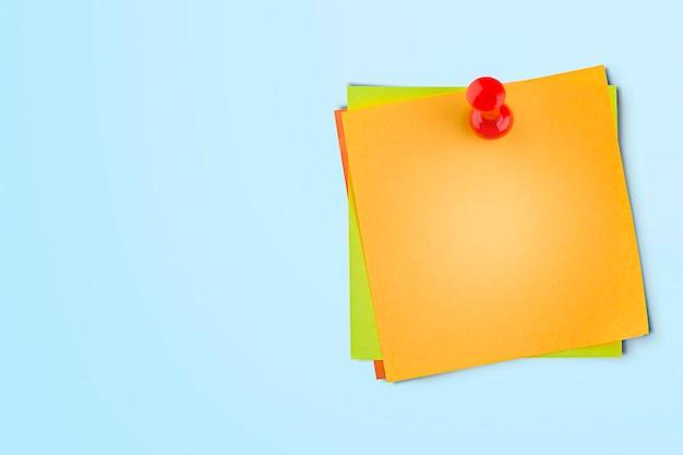 Notas adesivas em uma tachinha. fundo azul claro