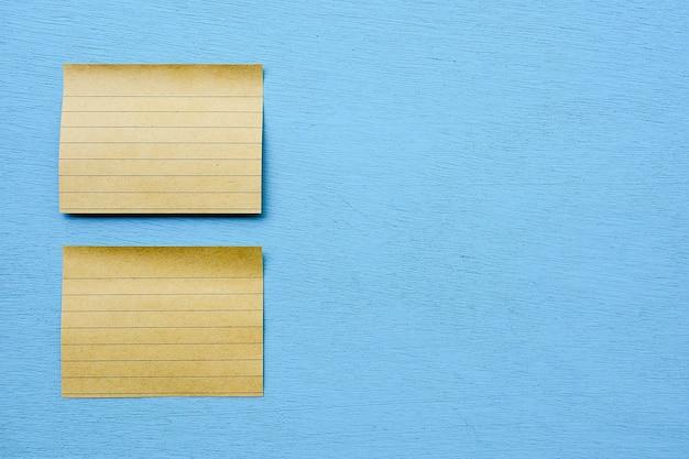 Notas adesivas marrons isoladas em azul