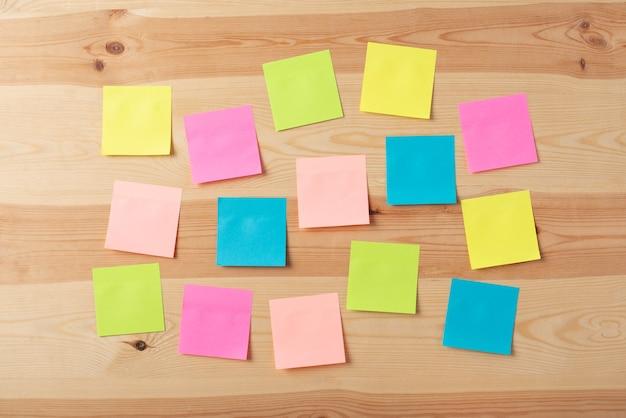Notas adesivas multicoloridas sem texto na mesa de madeira Foto Premium