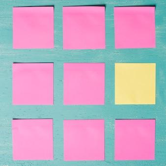 Notas adesivas rosa e amarelas sobre fundo texturizado de madeira