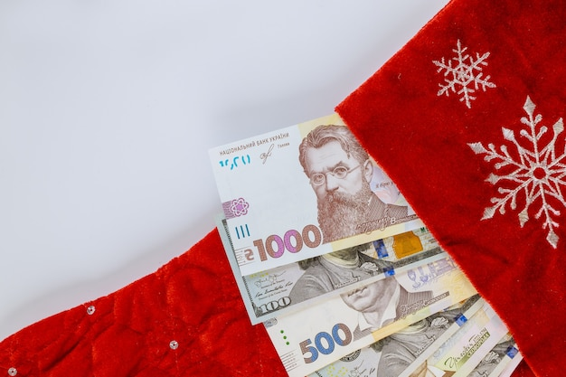 Notas americanas de cem dólares e hryvnia ucraniana em meias vermelhas de natal para presentes