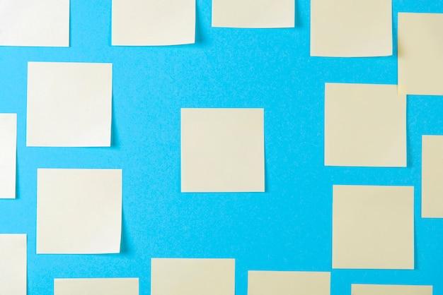 Notas auto-adesivas amarelas em branco no azul