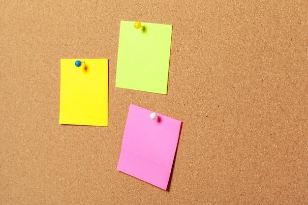 Notas auto-adesivas coloridas com alfinetes e espaço em branco, sobre fundo de cortiça