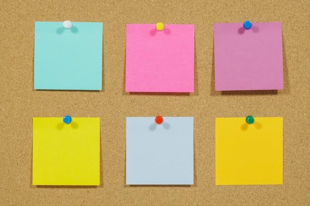 Notas auto-adesivas coloridas no quadro de avisos de cortiça