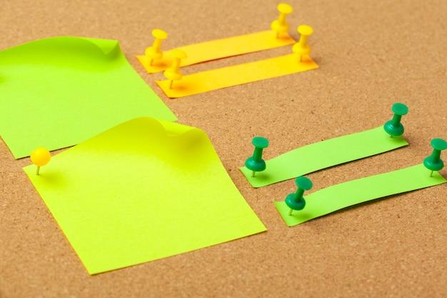 Notas auto-adesivas com alfinetes e espaço em branco na cortiça. escola ou conceito de negócio