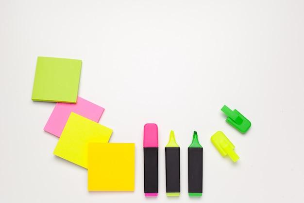 Notas auto-adesivas com marcadores, canetas coloridas, clipes de papel, deitado sobre um fundo branco