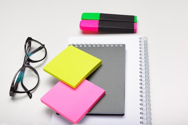 Notas auto-adesivas com marcadores, canetas coloridas, clipes de papel, deitado sobre uma mesa