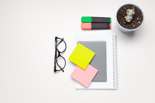 Notas auto-adesivas com marcadores, canetas coloridas, clipes de papel sobre uma mesa