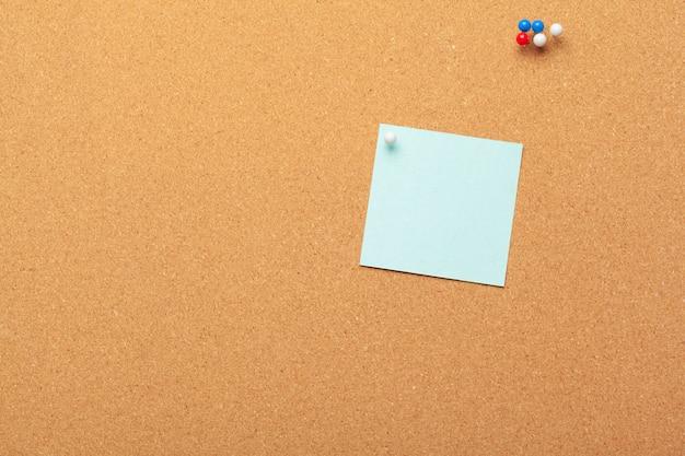Notas auto-adesivas com pinos e espaço em branco na cortiça. escola ou empresa