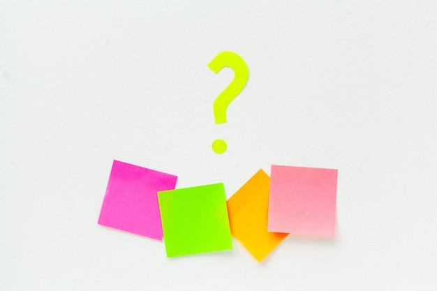 Notas auto-adesivas com pontos de interrogação sobre branco