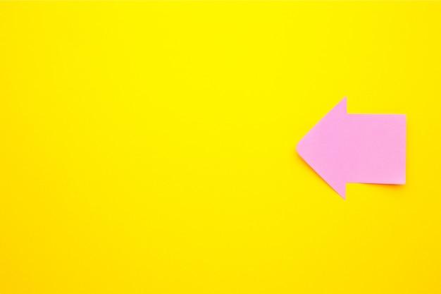 Notas auto-adesivas de papel em forma de seta em fundo amarelo