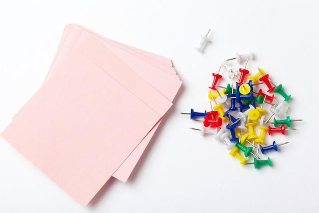Notas auto-adesivas e pinos em fundo branco