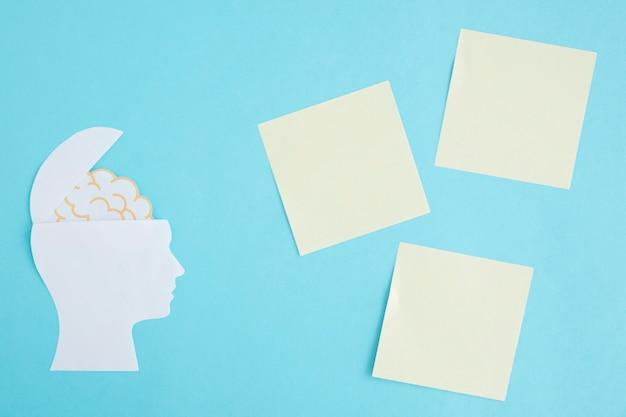 Notas auto-adesivas em branco com o cérebro na cabeça aberta sobre fundo azul