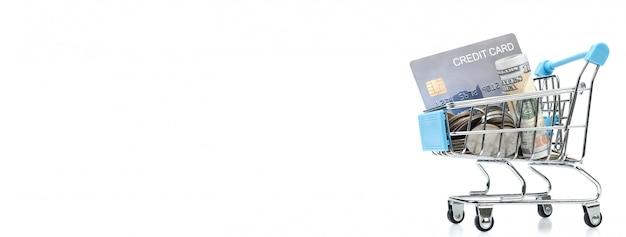 Notas, cartão de crédito e moedas no carrinho de compras