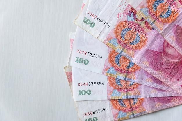 Notas chinesas de 100 yuan em leque na mesa de madeira