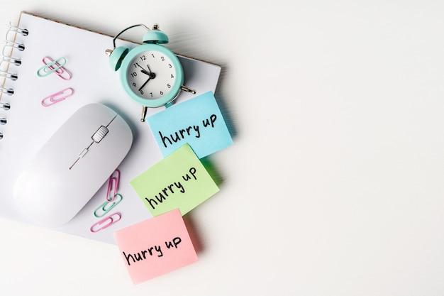 Notas coloridas apresse-se na área de trabalho com bloco de notas e despertador. conceito de planejamento do dia, cronograma