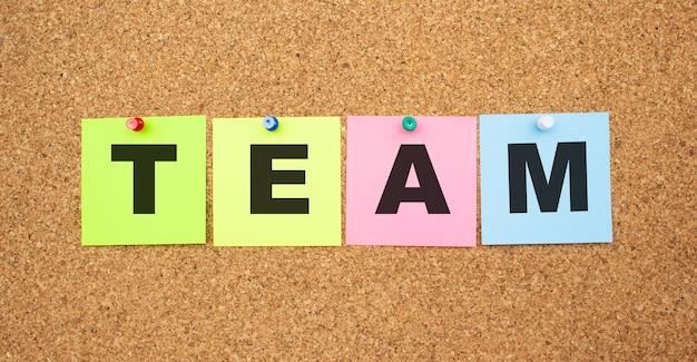Notas coloridas com letras fixadas em um quadro. palavra equipe. área de trabalho.
