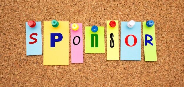 Notas coloridas com letras fixadas em um quadro. palavra patrocinador. área de trabalho.