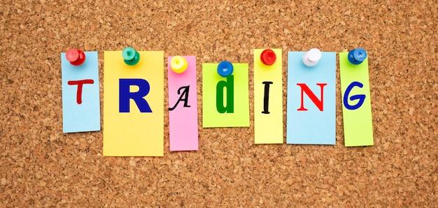 Notas coloridas com letras fixadas em um quadro. trading da palavra. área de trabalho.