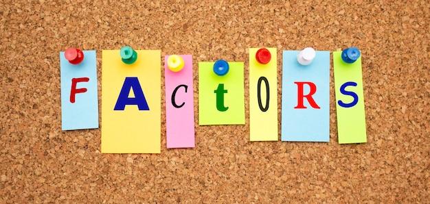 Notas coloridas com letras fixadas em um quadro. word factors