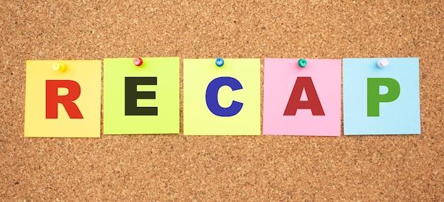 Notas coloridas com letras fixadas em um quadro. word recap. área de trabalho.