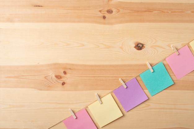 Notas coloridas penduradas em uma corda com um espaço de cópia para inscrição