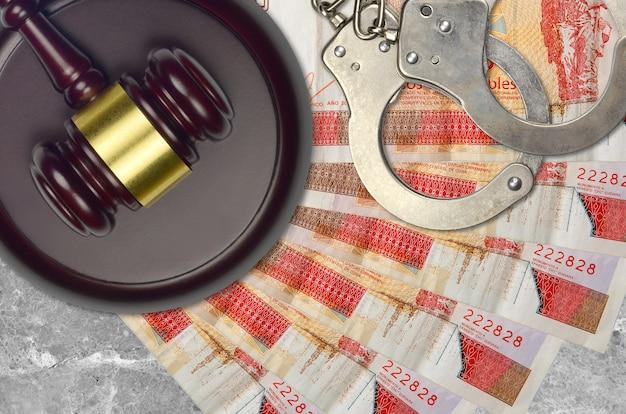 Notas conversíveis de 3 pesos cubanos e martelo do juiz com algemas da polícia na mesa do tribunal. conceito de julgamento judicial ou suborno. elisão ou evasão fiscal